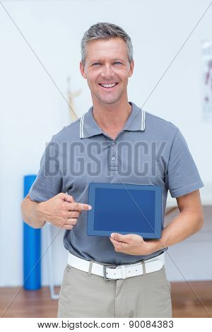 Smiling doctor showing digital tablet in medical office
