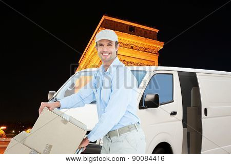 Confident delivery man pushing trolley of cardboard boxes against arc de triumphe in france