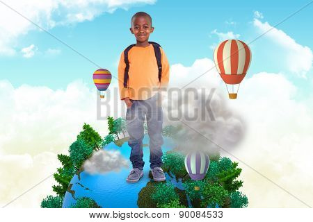Cute elementary pupil smiling at camera against cloud computing graphic with hot air balloons