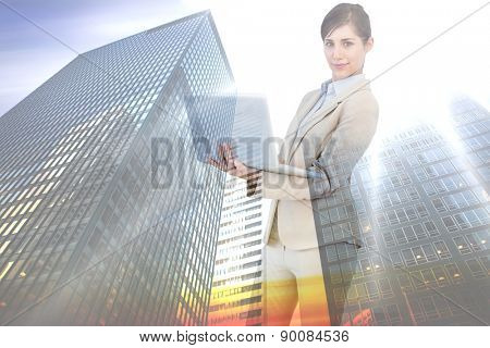 Confident young businesswoman with laptop against low angle view of skyscrapers at sunset