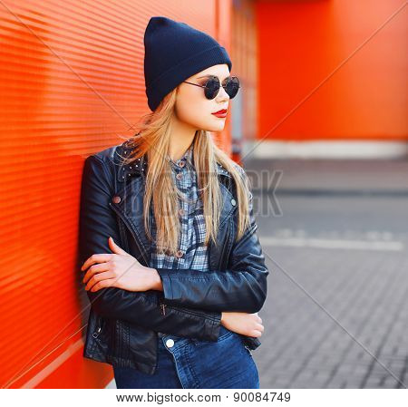 Street Fashion Concept - Stylish Woman In Rock Black Style Against A Red Urban Wall