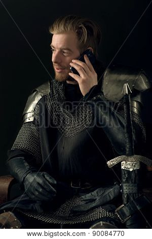 Ancient knight in metal armor talking on mobile phone