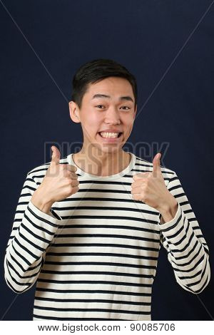 Smiling young Asian man giving the thumbs up signs and looking at camera