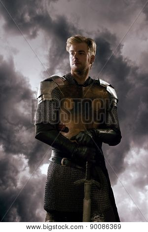 Ancient knight in metal armor with sword standing on a cloudy background