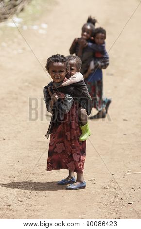 OROMIA, ETHIOPIA-APRIL 20, 2015: Unidentified child carries her sibling on her back in a small village in Ethiopia