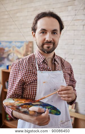 Modern artist with paintbrush and palette looking at camera in studio