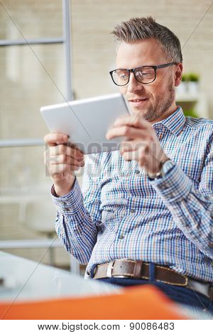 Restful businessman with touchpad sitting in office