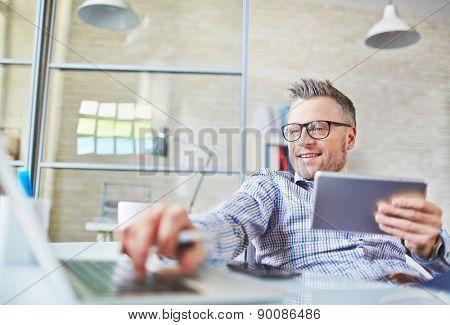 Mature businessman addicted to gadgets having break