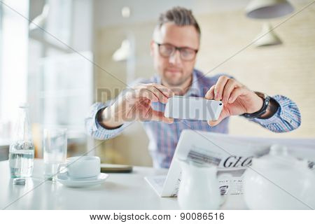 Businessman using smartphone to take photo of something in newspaper