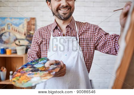 Happy artist holding palette with mixed colors while painting