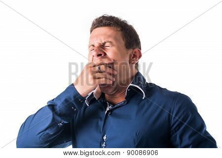 Good looking young man yawning, isolated