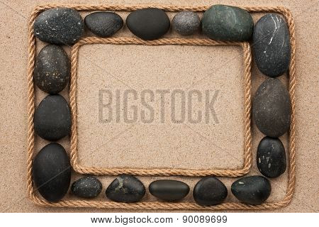 Beautiful Frame With Rope And Black Stones On Sand
