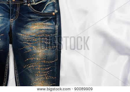 Trendy Jeans With Rhinestones Lies On White Silk