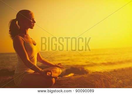 Woman Meditating In Lotus Pose On The Beach At Sunset