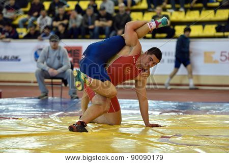 ST. PETERSBURG, RUSSIA - MAY 6, 2015: Esbolat Nurzhumbayev of Kazakhstan against unidentified Russian athlete during International freestyle wrestling tournament Victory Day