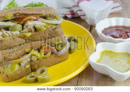 chicken and olive sandwich with mustard sauce and ketchup
