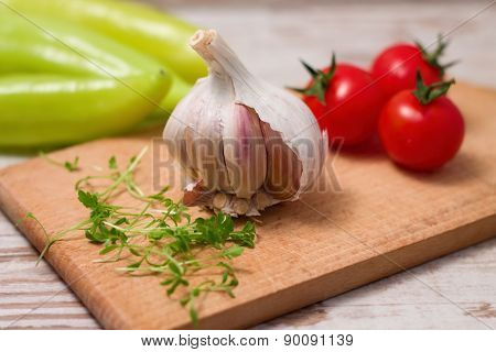 Garlic Head On Chopping Board With Cress And Tomatoes