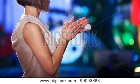 Woman clapping - stage in the background