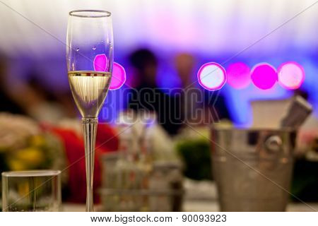 Glass with champagne lit by nightclub lights