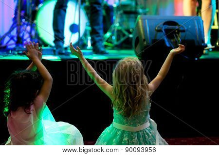 Two little girls in front of stage during rock concert