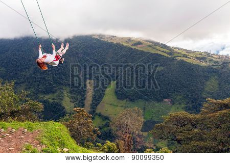 Happy European Woman Swinging In A Swing Placed Above Tungurahua Volcano, Andes Mountains, Ecuador