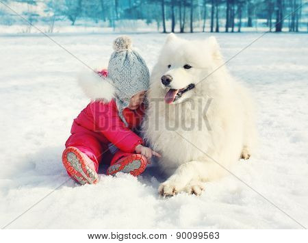 Child With White Samoyed Dog On The Snow In Winter Day