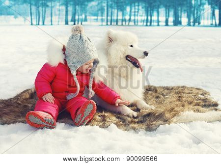 Happy Child With White Samoyed Dog On The Snow In Winter Day