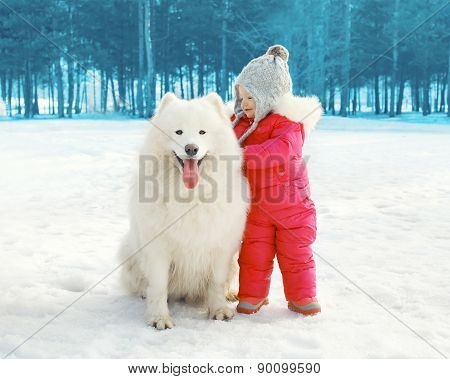 Portrait Of Happy Child With White Samoyed Dog In Winter Day