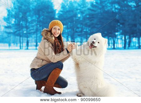 Portrait Of Happy Woman Owner Having Fun With White Samoyed Dog Outdoors In Winter Day