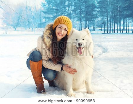 Portrait Of Happy Woman With White Samoyed Dog Outdoors On The Snow In Winter Day