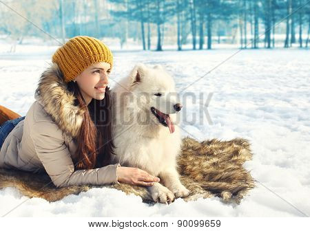 Portrait Of Woman And White Samoyed Dog Lying On The Snow In Winter Day