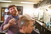 picture of facial piercings  - Portrait Of Male Barber Giving Client Haircut In Shop - JPG