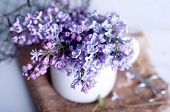 foto of hazy  - Bouquet of purple lilac spring flowers with an open book and vintage hazy editing - JPG