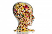 a head made of glass filled with many tablets. photo icon for drugs abuse and painkillers. poster