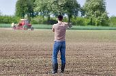 image of hoe  - Rear view of attractive farmer carrying hoe on shoulders in corn field in spring tractor in background - JPG