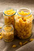 image of glass noodles  - Different types of yellow macaroni pasta in glass bowl on hessian fabric cloth - JPG