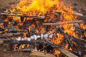 image of baked potato  - Baked potatoes covered with aluminum foil roasting in a bonfire with orange flames and firewood - JPG