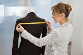pic of measurements  - Portrait Of Fashion Designer Measuring Suit With Measuring Tape - JPG
