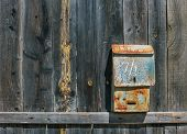 picture of mailbox  - Old shabby mailbox on green wooden fence - JPG