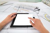 stock photo of blueprints  - Draftsman Hands With Blank Digital Tablet Over Blueprint In Office. Blueprints were created by photographer