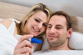 foto of pregnancy test  - Happy Couple Watching Pregnancy Test In Bedroom - JPG
