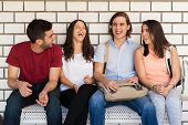 pic of sitting a bench  - Group of Latin college friends talking and having some fun while sitting in a bench in the school hallway - JPG