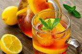 image of iced-tea  - lemon iced tea on brown wooden table with lemons around - JPG