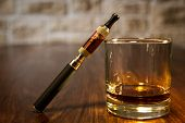 stock photo of electronic cigarette  - vintage still life with electronic cigarette and a glass of rum - JPG