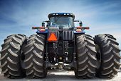 image of truck-cabin  - Blue farm tractor on huge wheels on a background of blue sky - JPG