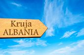 picture of albania  - Wooden arrow sign pointing destination KRUJA ALBANIA against clear blue sky with copy space available - JPG