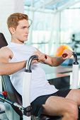 pic of concentration man  - Concentrated young man working out in gym - JPG