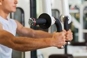 picture of concentration man  - Concentrated young and sporty man working out in gym - JPG