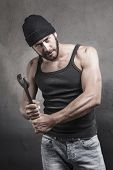 stock photo of thug  - Thug preparing to use a wrench as a weapon with a dangerous angry expression over a textured grey background looking at camera - JPG