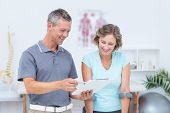 pic of crutch  - Woman using crutch and talking with her doctor in medical office - JPG